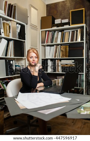 Young beautiful woman in his office
