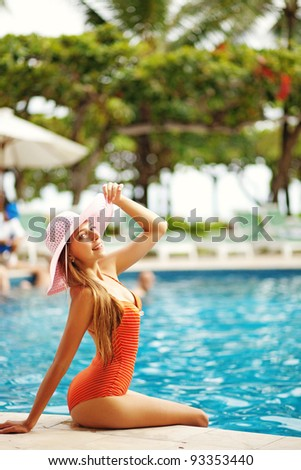 Young beautiful woman outdoors sitting near swimming pool