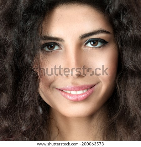 Young beautiful woman portrait with long curly hair posing in studio