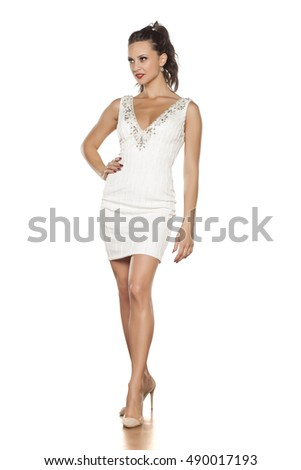 young beautiful woman posing in a white short dress and high heels