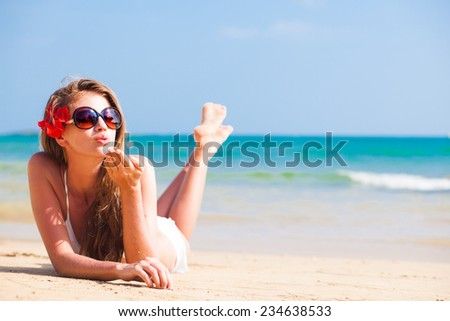 young beautiful woman relaxing at sunny tropical beach