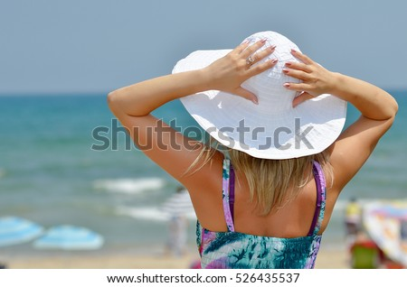 young beautiful woman relaxing on the beach in warm summer day