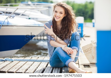 Young beautiful woman relaxing on the dock near the boat on a sunny day