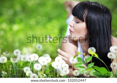 Young beautiful woman resting on fresh green grass