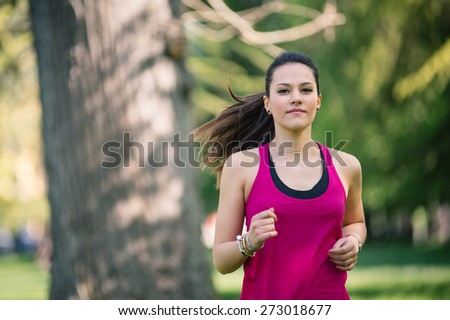 Young beautiful woman running outdoors in a park.