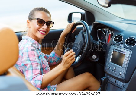 Young beautiful woman sitting in a convertible and is going to start the engine - the concept of buying a used car or a rental car