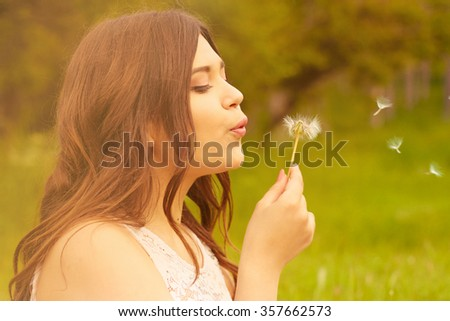 Young beautiful woman sitting in the woods on the grass and holding a dandelion. Spring.