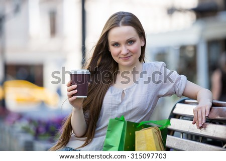 Young beautiful woman sitting on a bench on the street with coffee cup in hand and shopping bags. Drinking coffee and smiling.