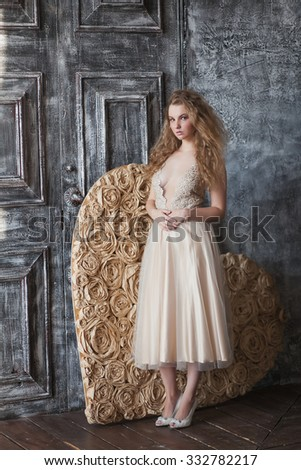 Young beautiful woman sitting on the background of a large paper heart