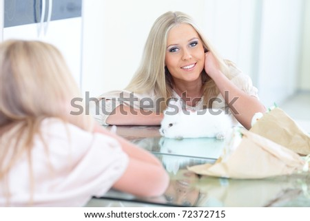 Young beautiful woman smiling to herself in mirror with rabbit