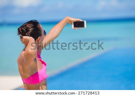 Young beautiful woman taking selfie with phone outdoors during beach vacation