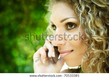 Young beautiful woman talking on the mobile phone at park