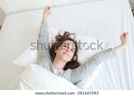 Young beautiful, woman waking up fully rested.