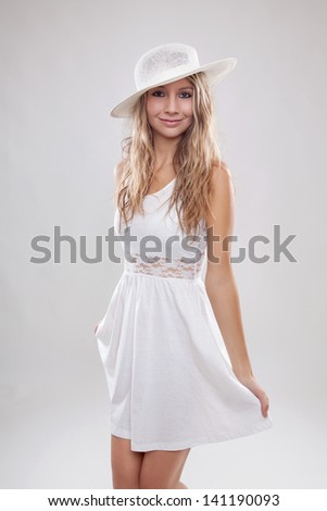 Young beautiful woman wearing a white dress and hat
