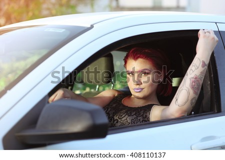young beautiful woman with bright make up and lots of tattoos in the white car