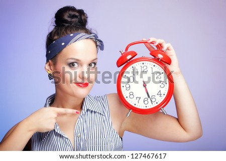 Young beautiful woman with red alarm clock blue background. Time management concept