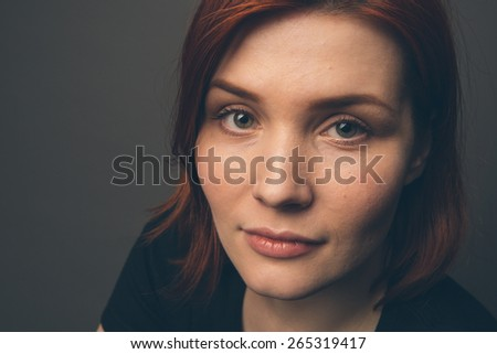 Young beautiful woman with red hair and smile portrait studio on dark grey background