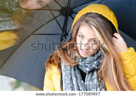 Young beautiful woman with umbrella wearing warm yellow coat