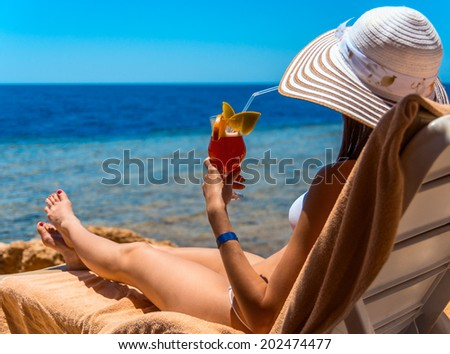Young beautiful woman woman is on a chaise longuer on the coast of sea in hat