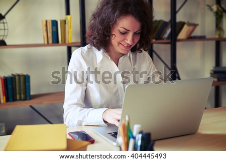 Young beautiful woman working at the table, with her laptop