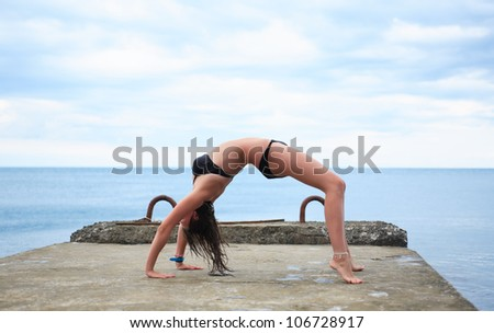 Young beauty teenage girl doing exercise on pier near sea