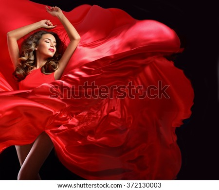 Young beauty woman in red waving flying  dress. Dancer in silk dress.