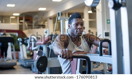 Young black african man portrait exercising at the gym.