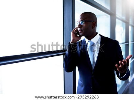 Young Black American Businessman Talking to Someone on Mobile Phone Beside the Glass Window Inside the Building.