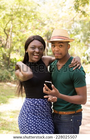 Young Black couple using cellphone and taking selfies