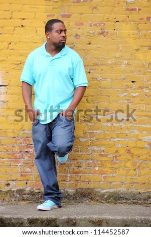 Young black man next to a yellow brick wall.