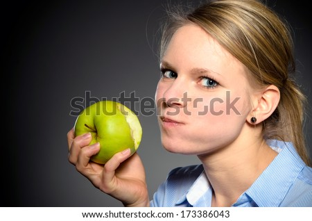 young blond woman eats joyfully a green apple