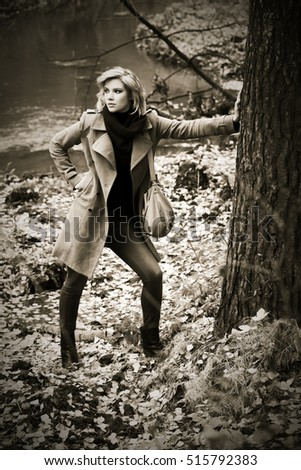Young blond woman in classic coat walking in autumn forest. Stylish fashion model with handbag outdoor