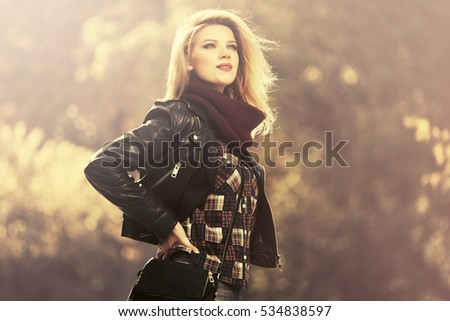 Young blond woman in leather jacket in autumn park Stylish fashion model outdoor