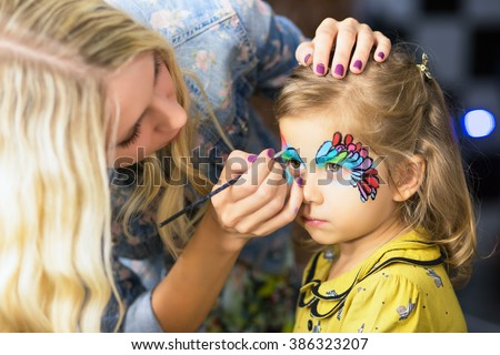 Young blond woman painting the face of a little girl