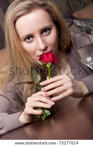 Young blonde girl with a red rose