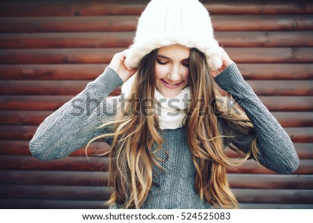 Young blonde happy smiling surprised girl in grey sweater and white warm hat and scarf outdoor closeup portrait. Cold outside. Winter clothes