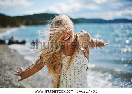 Young blonde laughing near the seaside