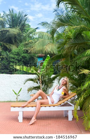 Young blonde woman at tropical resort in front of palm tree