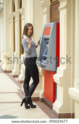 Young blonde woman in a red coat with a phone in his hand on the background of the mall ATM