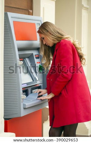 Young blonde woman in a red coat withdraw cash from an ATM in a shopping center