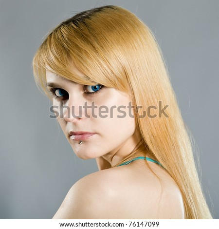 young blue-eyed blonde on a gray background