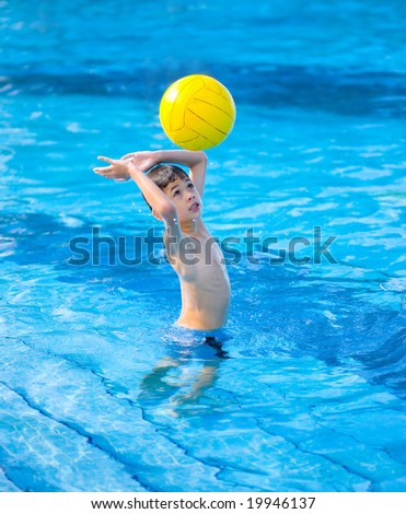 Young boy about to hit a ball while in the swimming pool