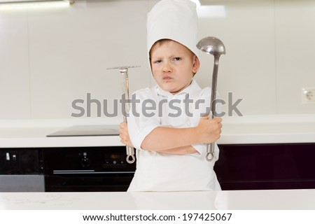 Young boy chef protecting his secret recipe standing gripping his utensils with folded arms and a pugnacious expression