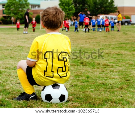 Young boy child in uniform watching organized youth soccer or football game from sidelines