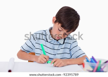 Young boy drawing against a white background