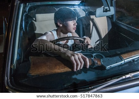 Young boy driving a car at night. boy looking in the rearview mirror. night on the highway. car headlights behind. boy wary. boy stole the car. boy armed with a gun. boy takes gun. scared boy