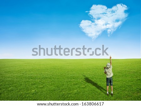 young boy green grass field pointing blue sky with clouds in shape of heart - love concept