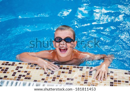 Young boy is swimming in swimming pool