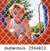 Young boy looking through fence playing prisoner - stock photo