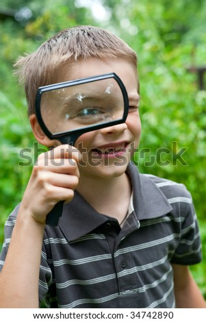 Young boy looking thru hand magnifier, shallow DOF